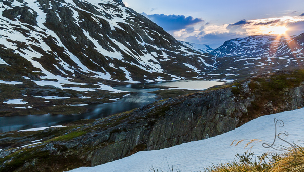 Sun setting over a still lake surrounded by snow-speckled hills in Norway | LotsaSmiles Photography
