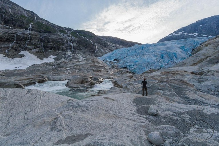 Aaron standing in front of the Nigardsbreen glacier in Norway | LotsaSmiles Photography