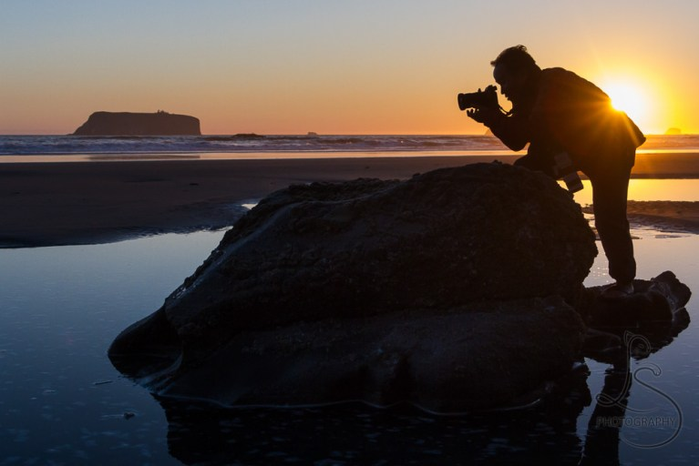Silhouette of our friend steadying himself on a rock on the beach for a photo with the sunset behind him | LotsaSmiles Photography