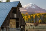 A barn stuffed with hay sits in front of Mount Adams at dusk