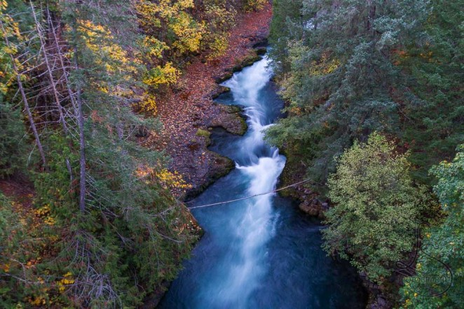 A river, blurred in motion, flowing between autumn banks | LotsaSmiles Photography