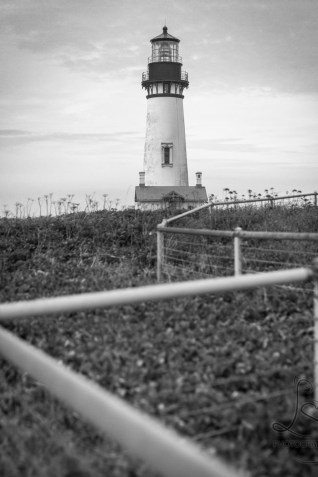 The Yaquina Lighthouse behind the zig zag line of a fence near Newport, Oregon | LotsaSmiles Photography