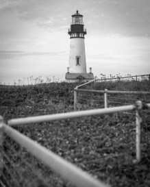 The Yaquina Lighthouse stands behind the zig zag line of a fence near Newport, Oregon