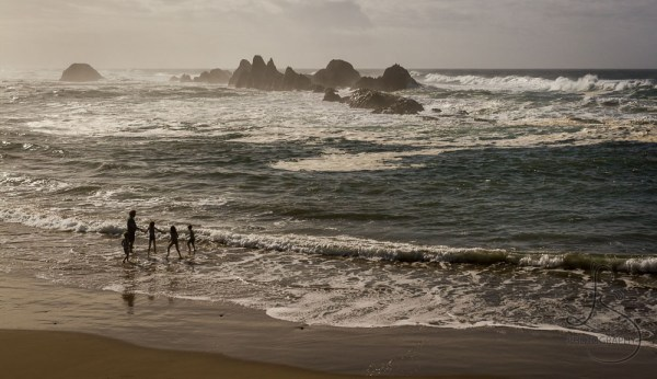 A family in silhouette, playing in the shallow waves near Newport, Oregon | LotsaSmiles Photography