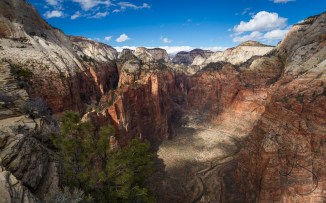 A few puffy clouds dapple the valley, viewed from atop the famous Angels Landing in Zion National Park