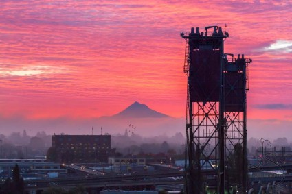 The sun rises over Mount Hood, illuminating the clouds in pinks and purples behind the silhouetted Hawthorne Bridge.
