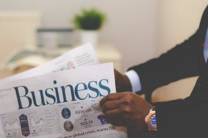 a man holding and reading a business magazine