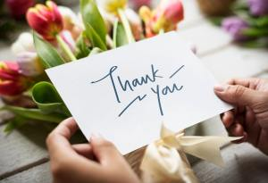 A thank you card in a woman's hands with flowers in the background happy customer