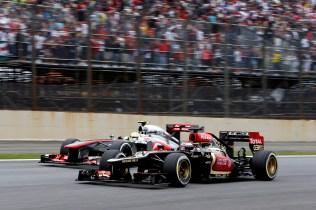 Heikki Kovalainen, Lotus E21 Renault, passes Sergio Perez, McLaren MP4-28 Mercedes.