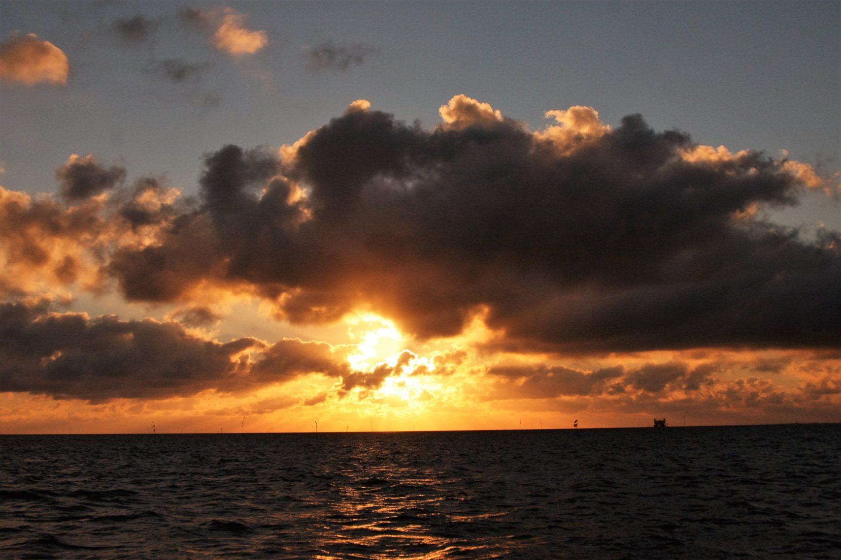 Ondergaande zon met donkere wolken boven zee tijdens zeilvakantie op de Nederlandse Waddenzee