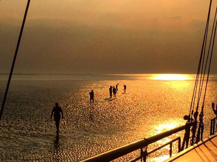 Wadlopen tijdens de zonsondergang tijdens een zeilvakantie op de Waddeneilanden.