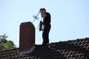 chimney sweep on roof inspecting chmney