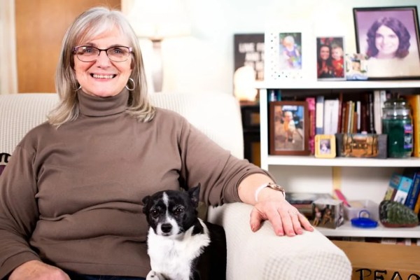 An older woman sharing her chair with a small black and white dog as part of a video testimonial series produced by video marketing company, Loudbyte