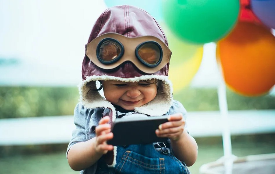 cut little boy smiles at his phone while wearing an old-fashioned pilots hat with goggles for a video testimonials article written by Loudbyte