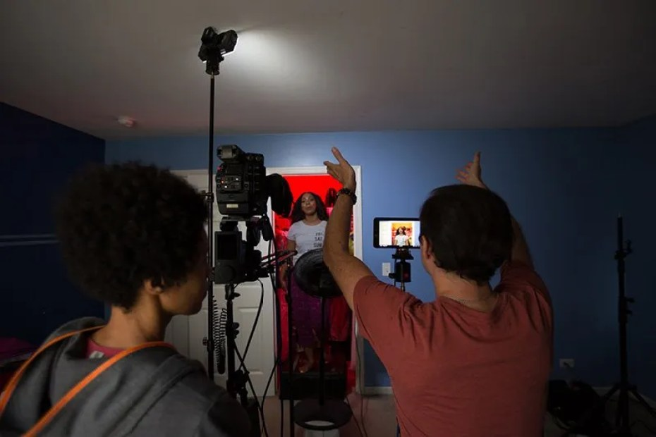 Director working with singer who is standing inside of a walk-in closet lit with red light as part of a music video