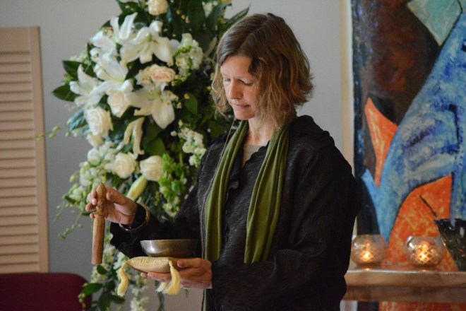 Unitarian Universalist Congregation of Sterling Reverend Anya Sammler-Michael rings a bowl 50 times to remember the people slain in Orlanda. (Renss Greene/Loudoun Now)