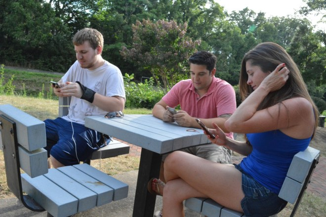 From left, RJ Jacobs, Gui Gomes, and Alini Correia catch Pokémon at Georgetown Park on Tuesday afternoon. Gomes and Correia, who came together, had never met Jacobs before. (Renss Greene/Loudoun Now)