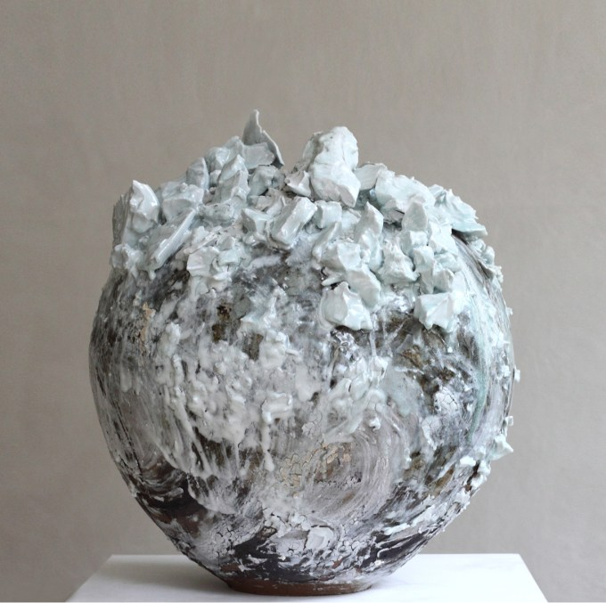A large moon jar by Akiko Hirai. The post is white and brown and has large chunks of glaze on it.