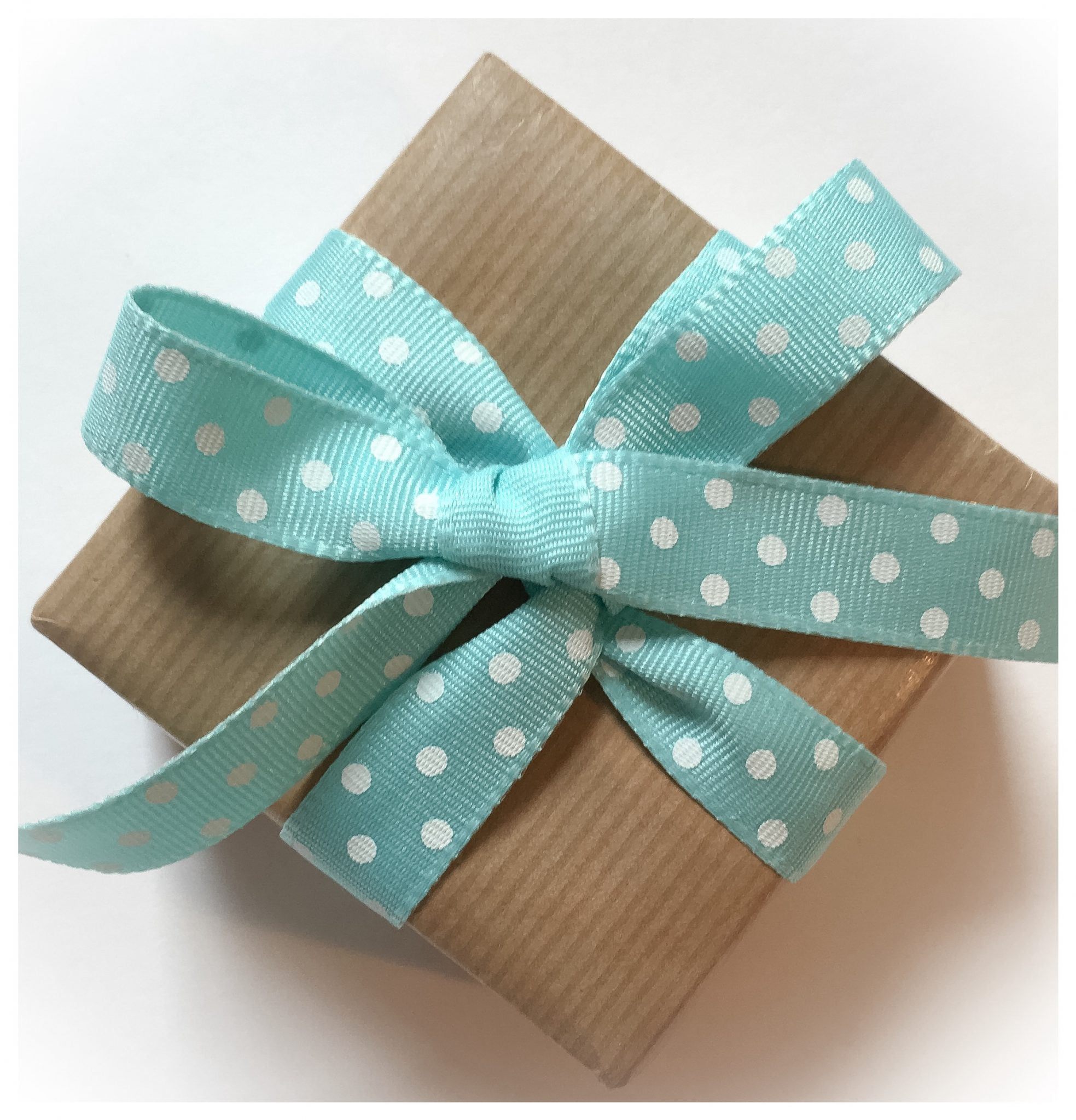 Parcel wrapped in kraft giftwrap with a spotty ribbon