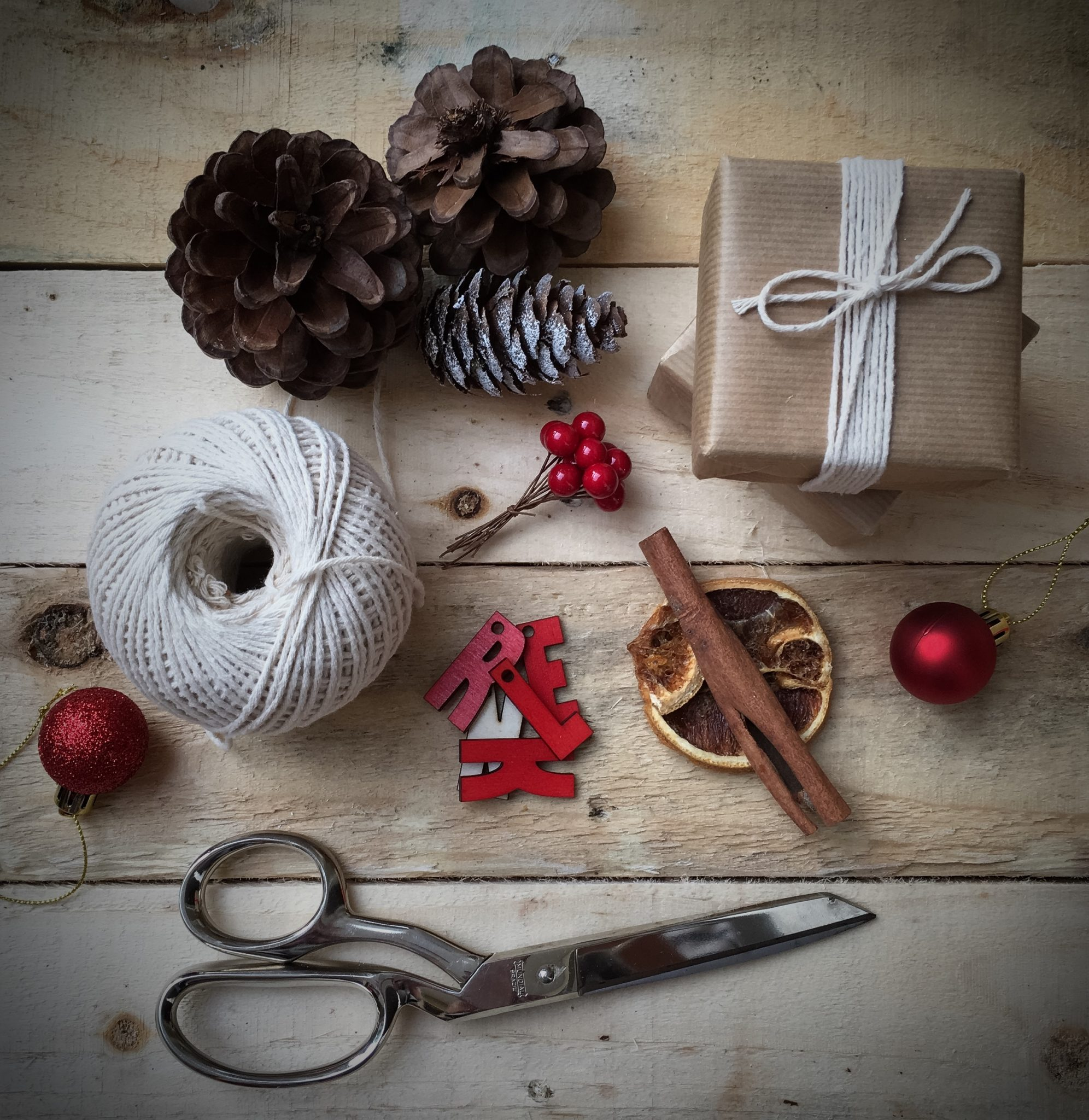 A picture of a brown parcel wrapped up with string, scissors, baubles, cones and cinnamon sticks