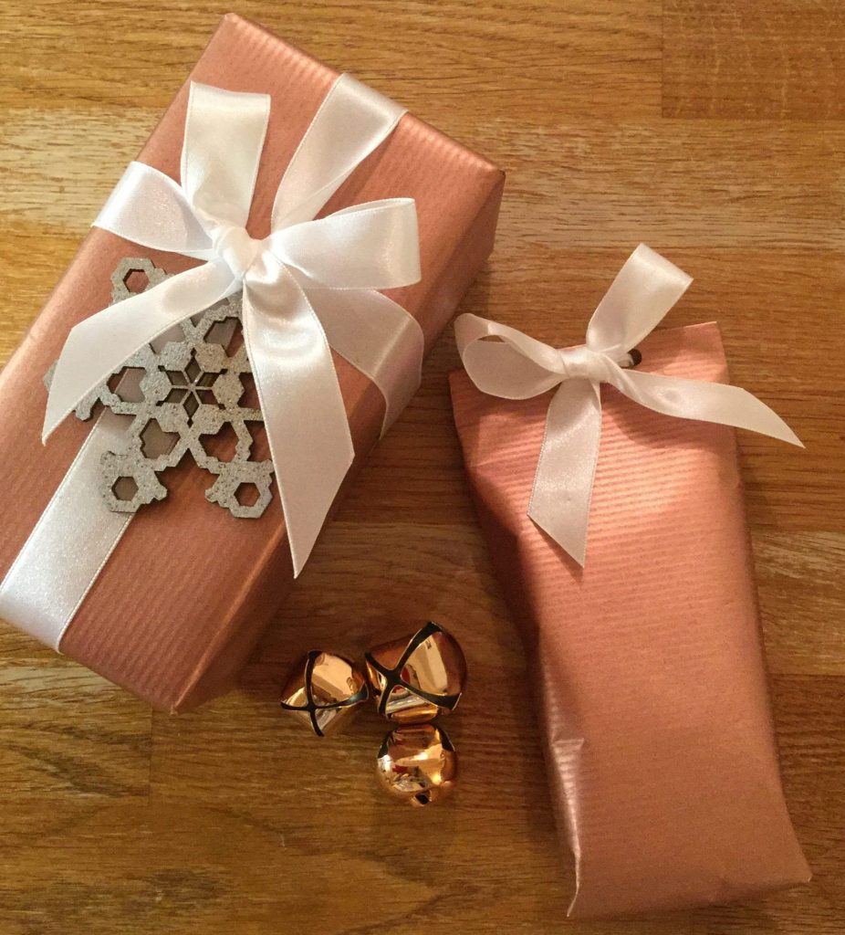 Two gifts wrapped with copper coloured giftwrap, white ribbon and snowflake decoration