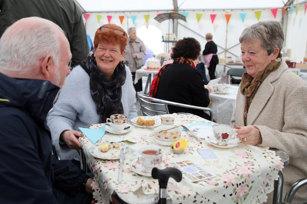 Three people sat round a table laid with a decorative table cloth and fine china