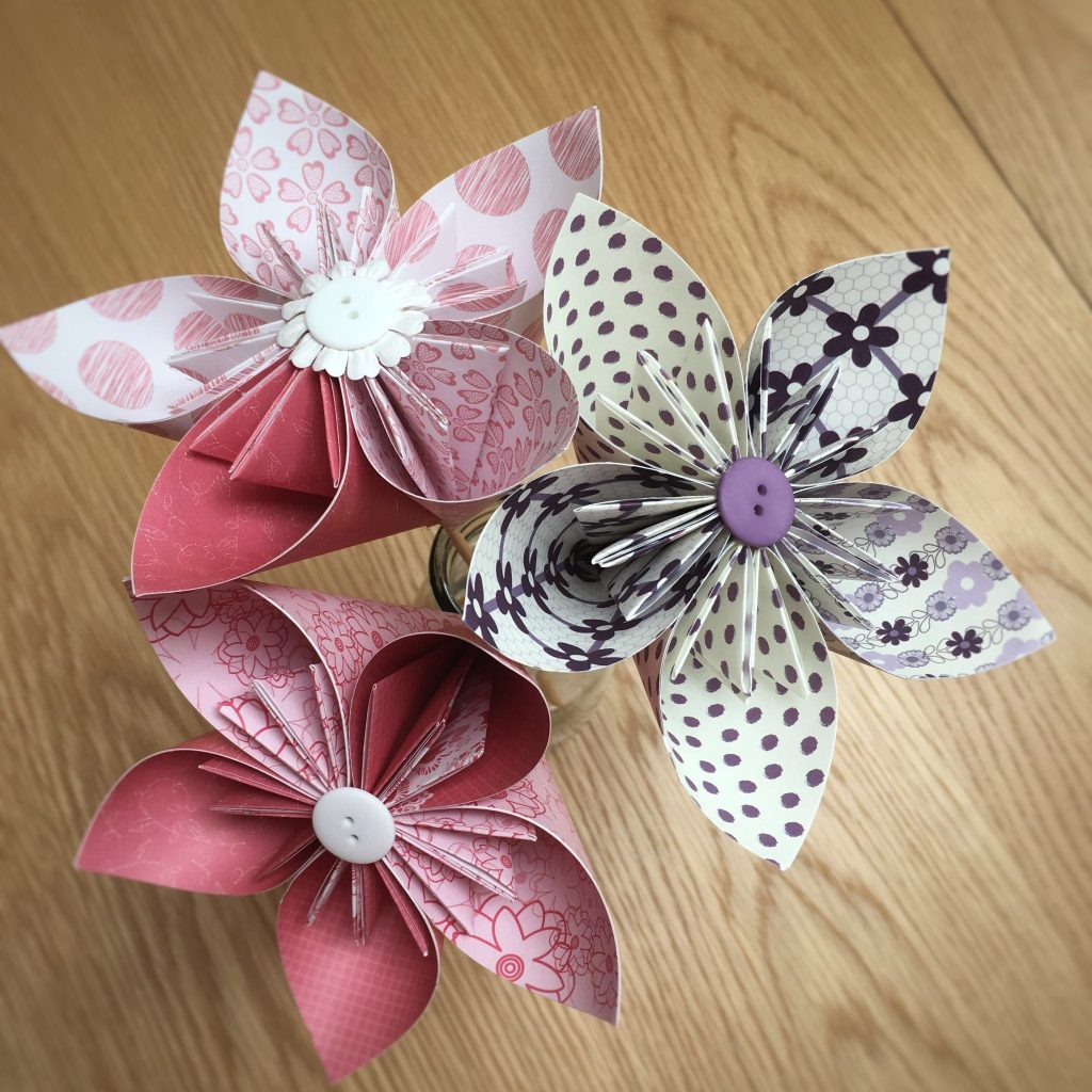Three large decorative paper kusudama flowers using pink and purple craft papers