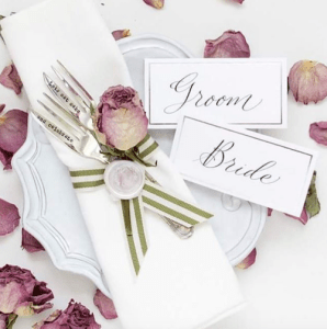A white napkin held together with striped ribbon and sealed with a wax seal. A rose used as decoration and tags with Bride & Groom written on them