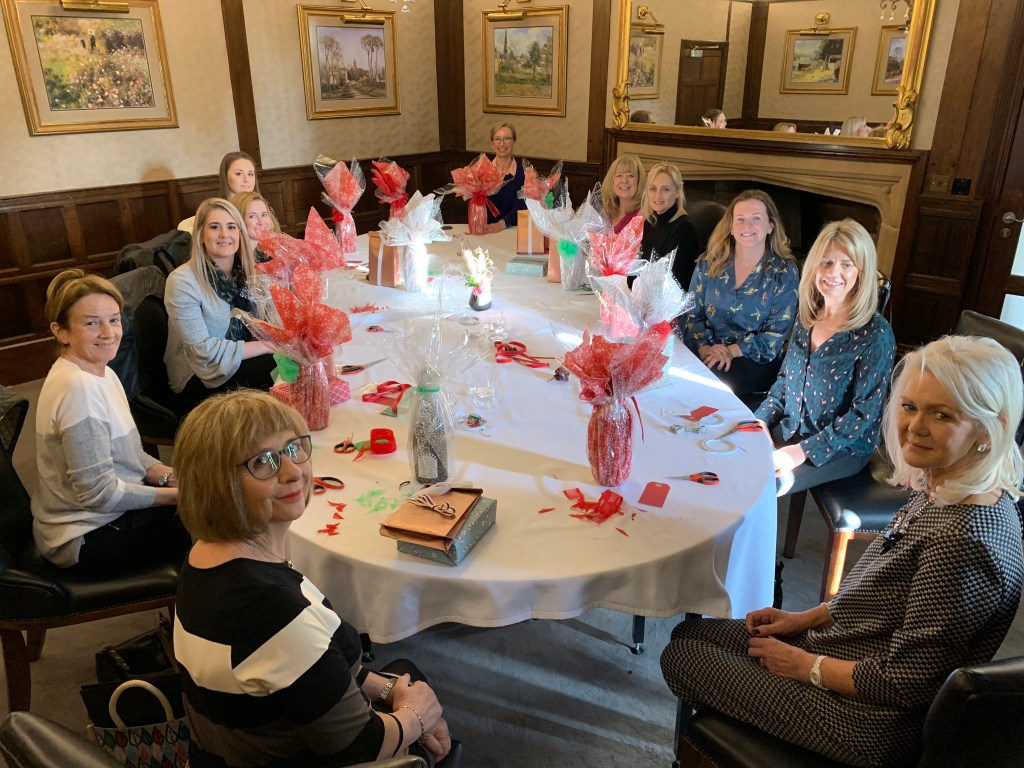 A group of ladies sat at a table with their giftwrapped creations including boxes and bottles