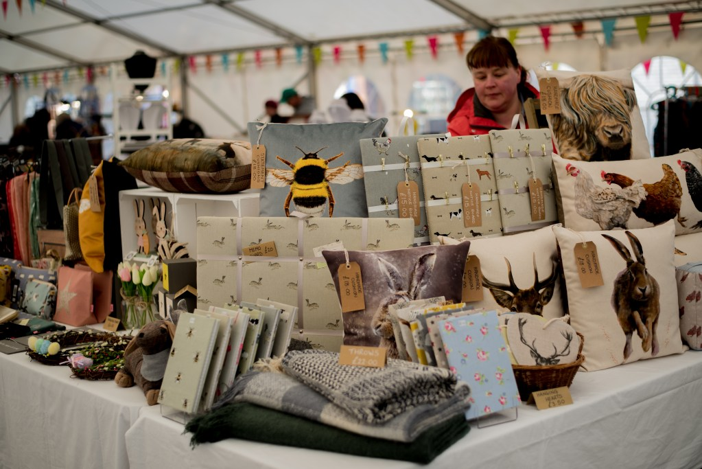 Homeware & gifts displayed on tables with Lynn (founder) behind