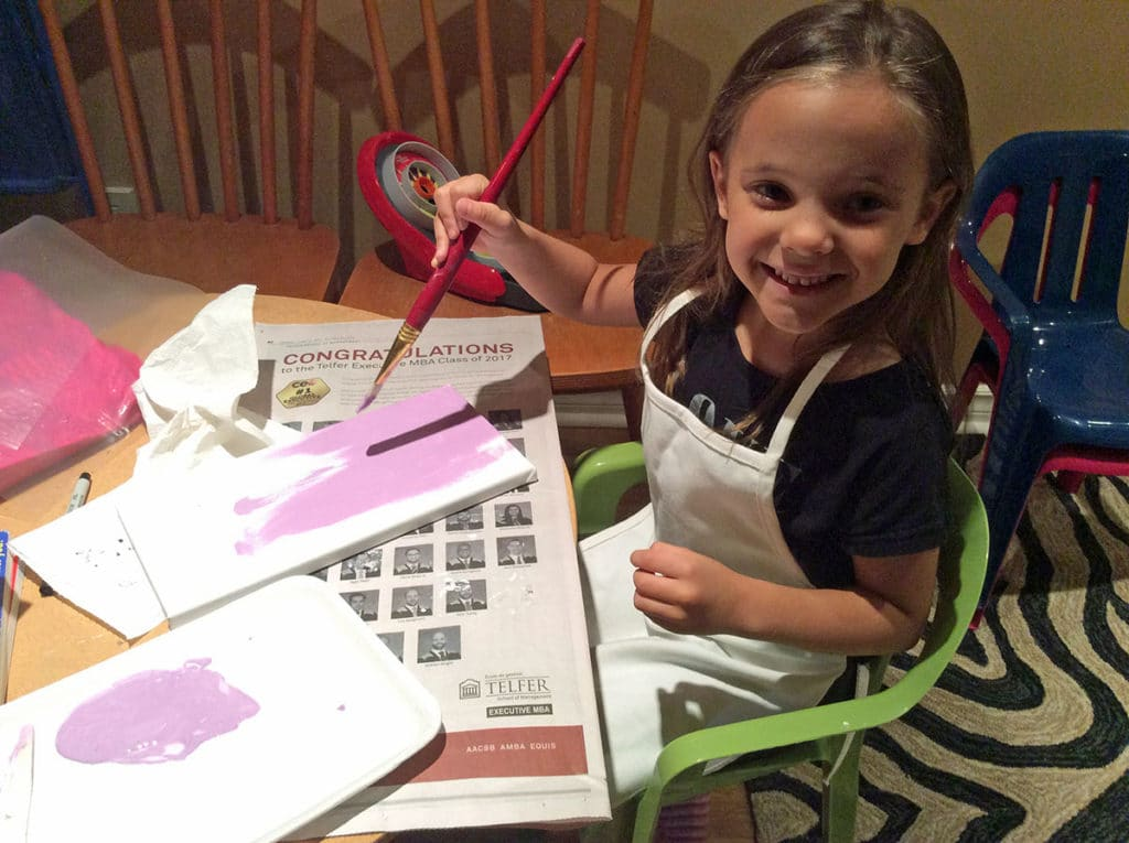 child painting a canvas with acrylics