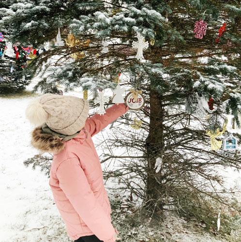 Joy ornament on outdoor tree