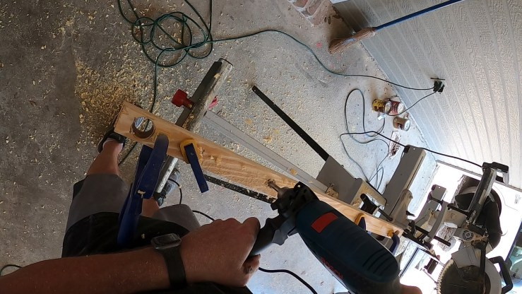 Drilling the holes for the tubing to be threaded through the boards for the Halloween DIY faux wrought iron fence.