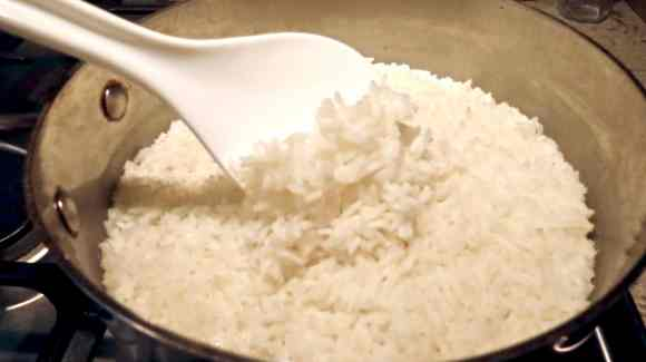 A pot of white rice with a white spoon scooping rice up.
