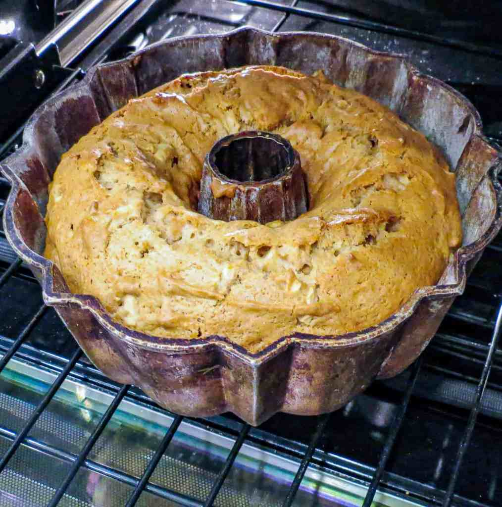 A bundt pan with a fresh apple cake in the oven.