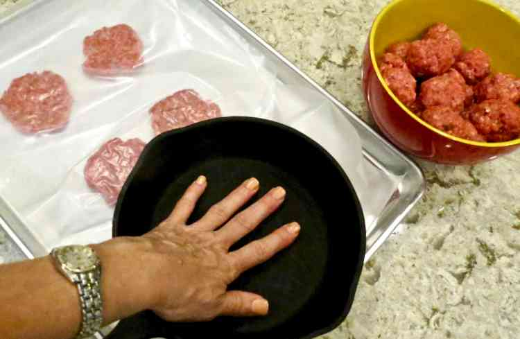 Hamburger patties pressed between wax paper with an iron skillet.