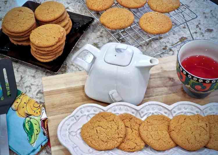 A dish of tea cakes beside a teapot.