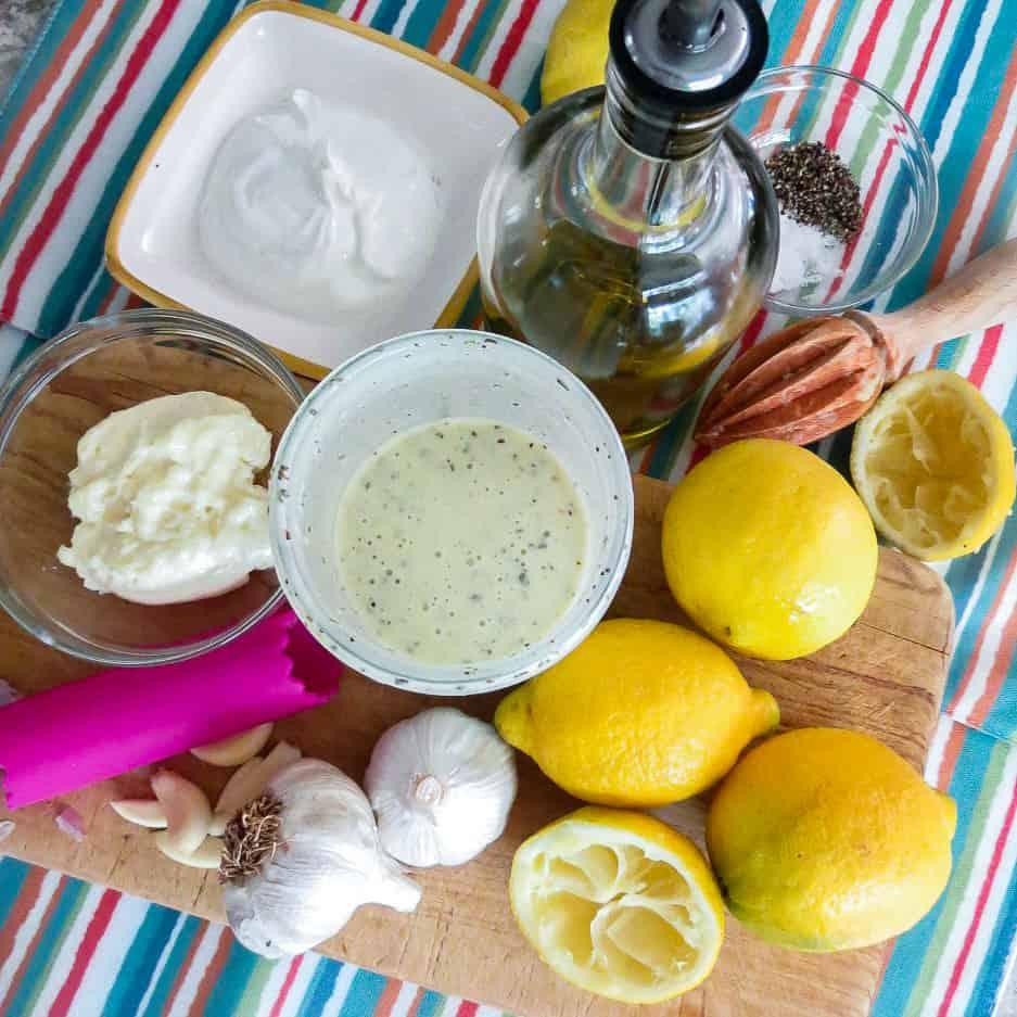 Ingredients for lemon greek yogurt salad dressing on a board for Chicken Salad With Green Peas.