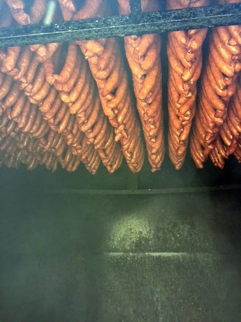 Sausage links hanging from the. ceiling of a smoke house.