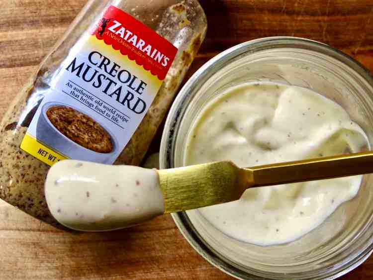 Overlooking Homemade Mayonnaise With A Creole Kick in a glass mason jar with a bottle of Zatarain's Creole Mustard next to it.