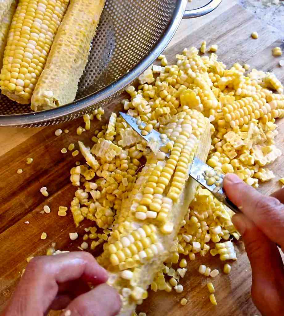 Cutting fresh corn from cob on wooden cutting board