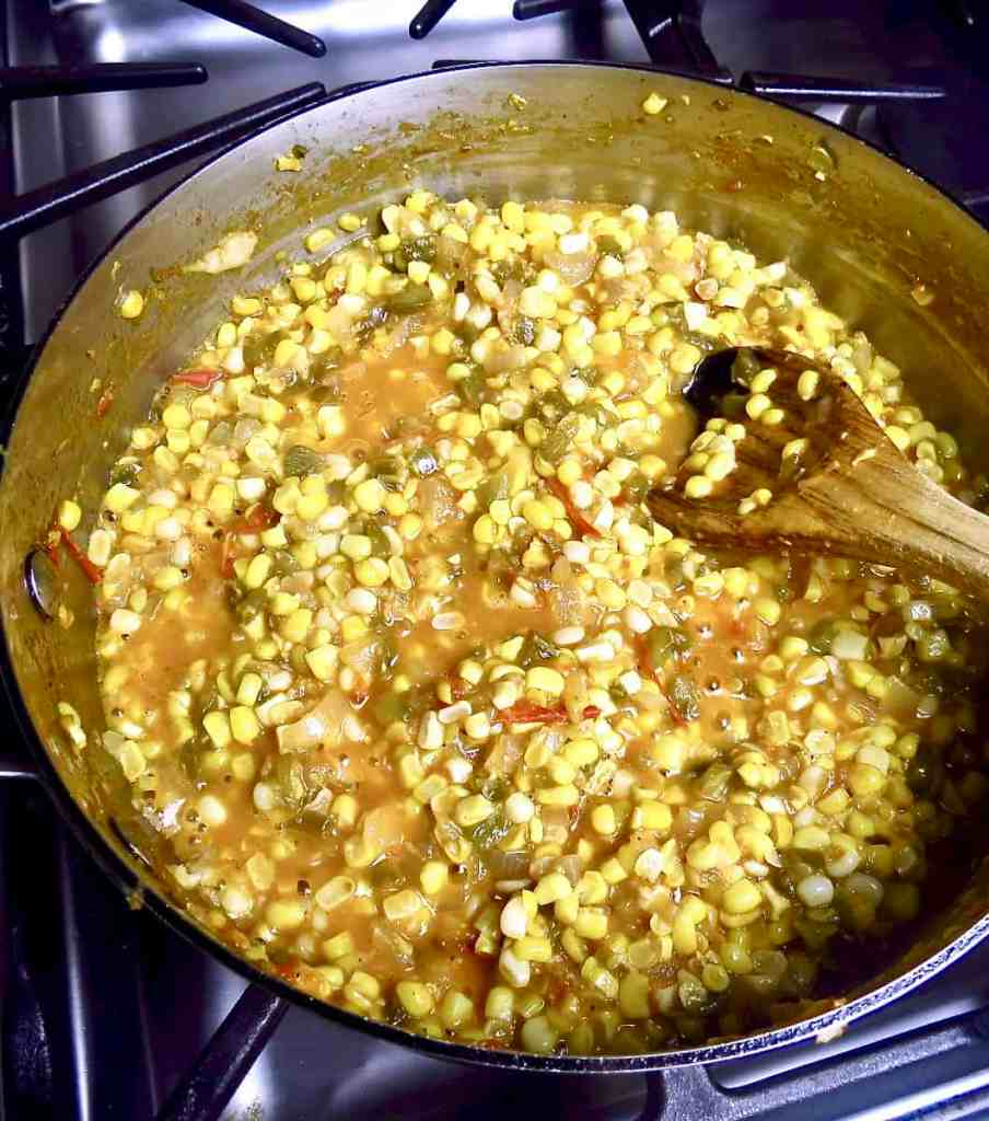 Stirring a pan of corn macque choux with a wooden spoon.