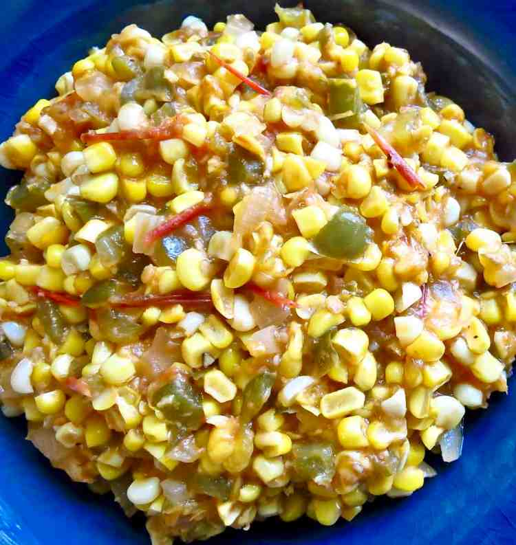 A close-up of a blue bowl full of corn maque choux.