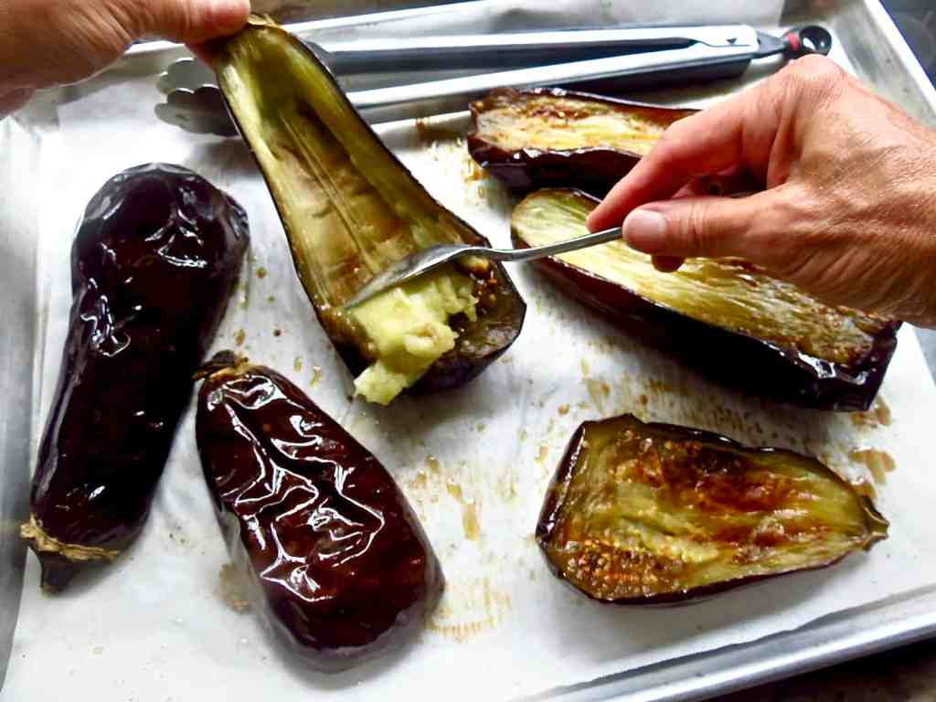 Scooping out eggplant from roasted purple shells with a spoon.