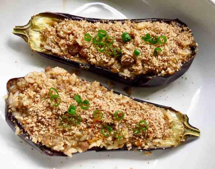 Dish with 2 eggplant shells stuffed with Eggplant Rice Dressing.