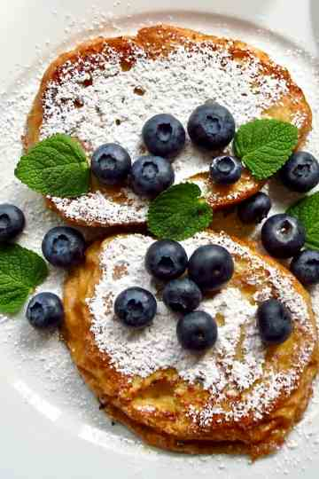French toast with powdered sugar and blue berries on a white plate.