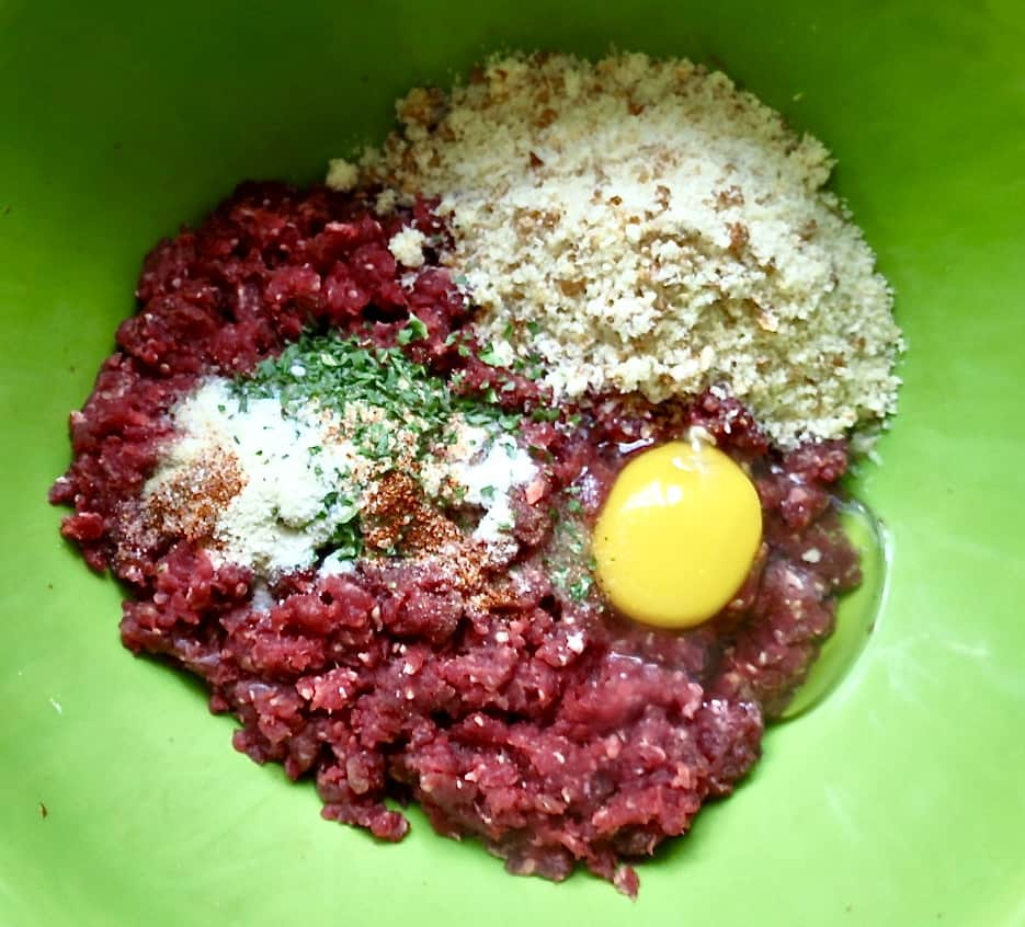 Ground meat with raw egg, seasonings, and breadcrumbs in green bowl.