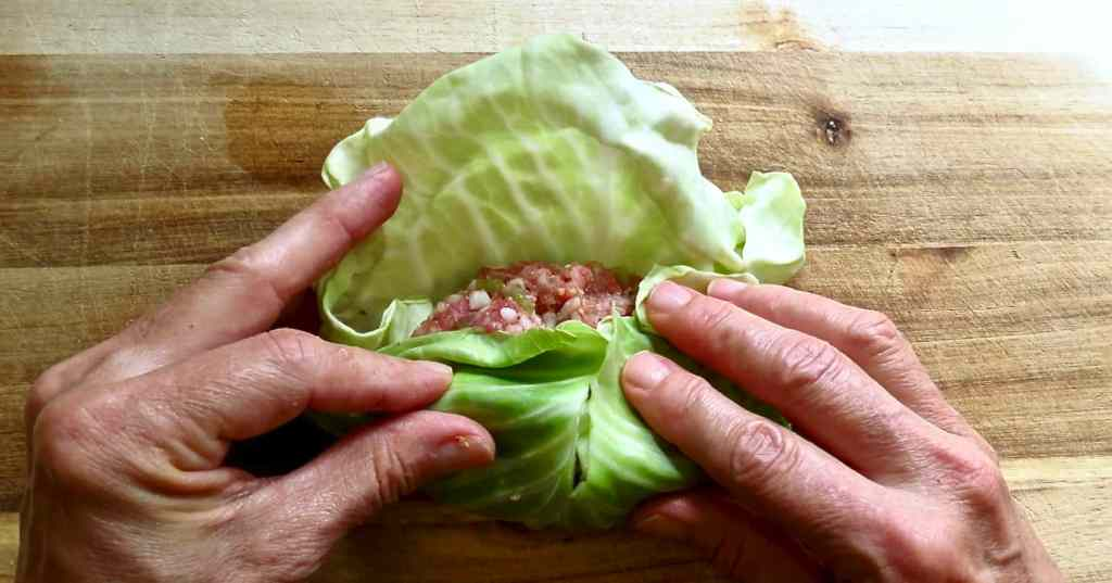 Two hands rolling up a roll of ground meat in a green leaf.