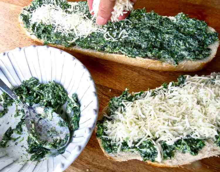 Two loaves of French Bread spread with spinach mix from a bowl of spinach mix and topped with white cheese on bread.