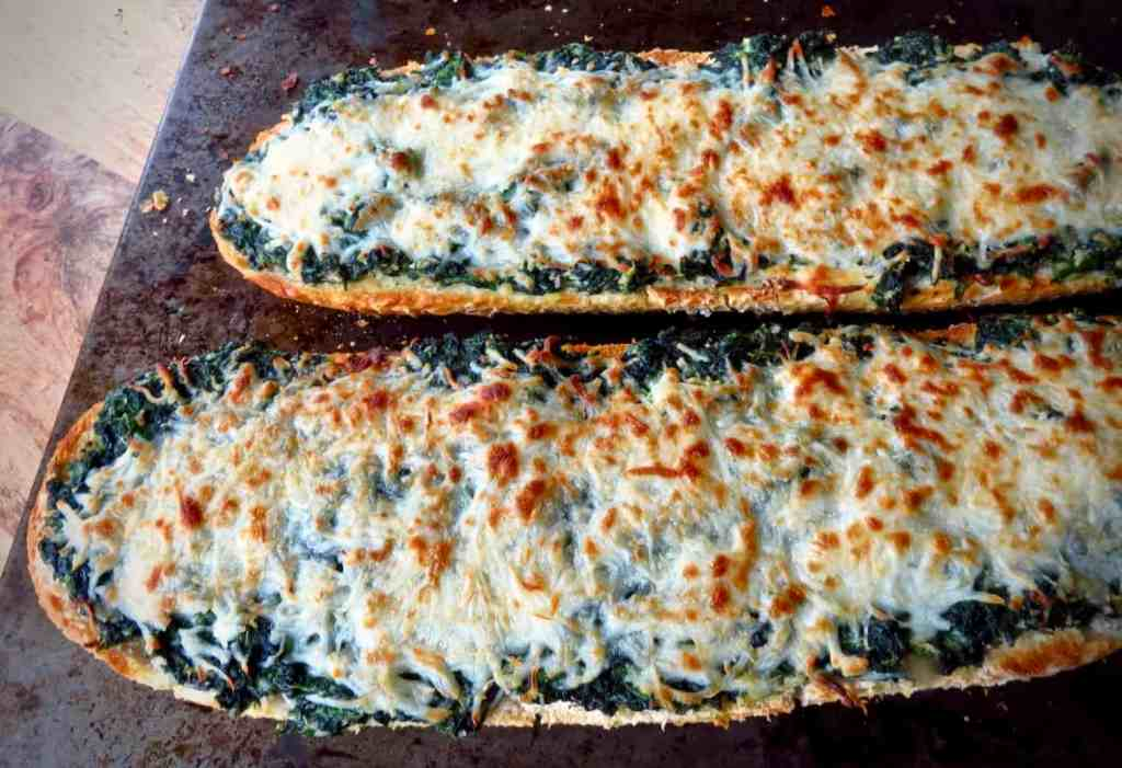 Two half loves of Spinach bread with cheese browned from the oven.